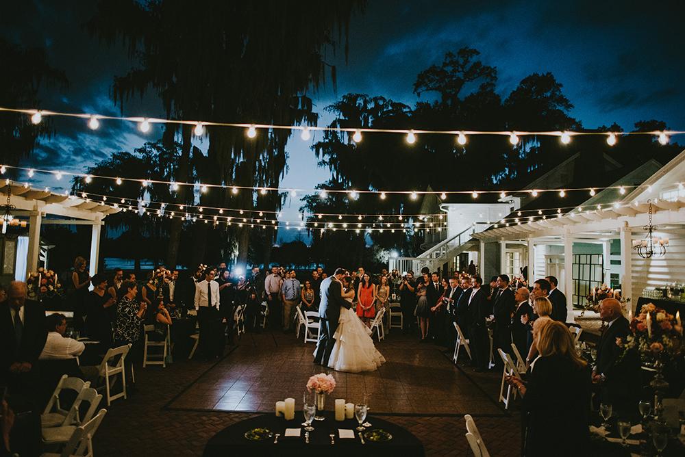 Cypress Grove Estate House, Outdoor Wedding, Lakeside Wedding, Central Florida Wedding Venues, Orlando Wedding Venues, market lighting, white reception chairs, first dance, wood dance floor, evening reception