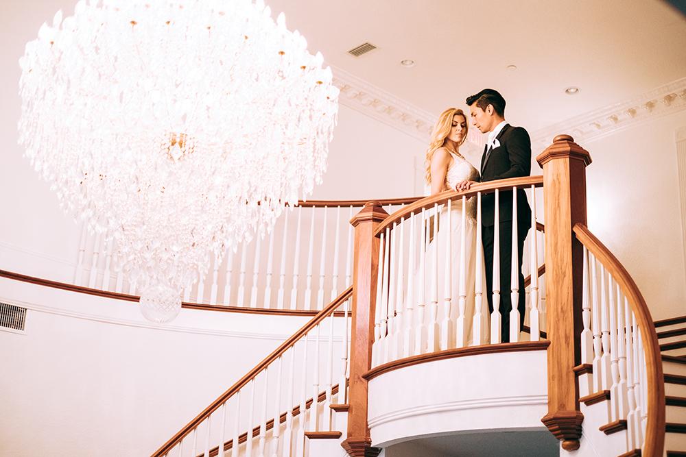 grand staircase, twin staircase, luxury venue, indoor venue, indoor reception, chandelier, ballroom wedding, central florida wedding venue, luxmore grande estate, bride and groom photos