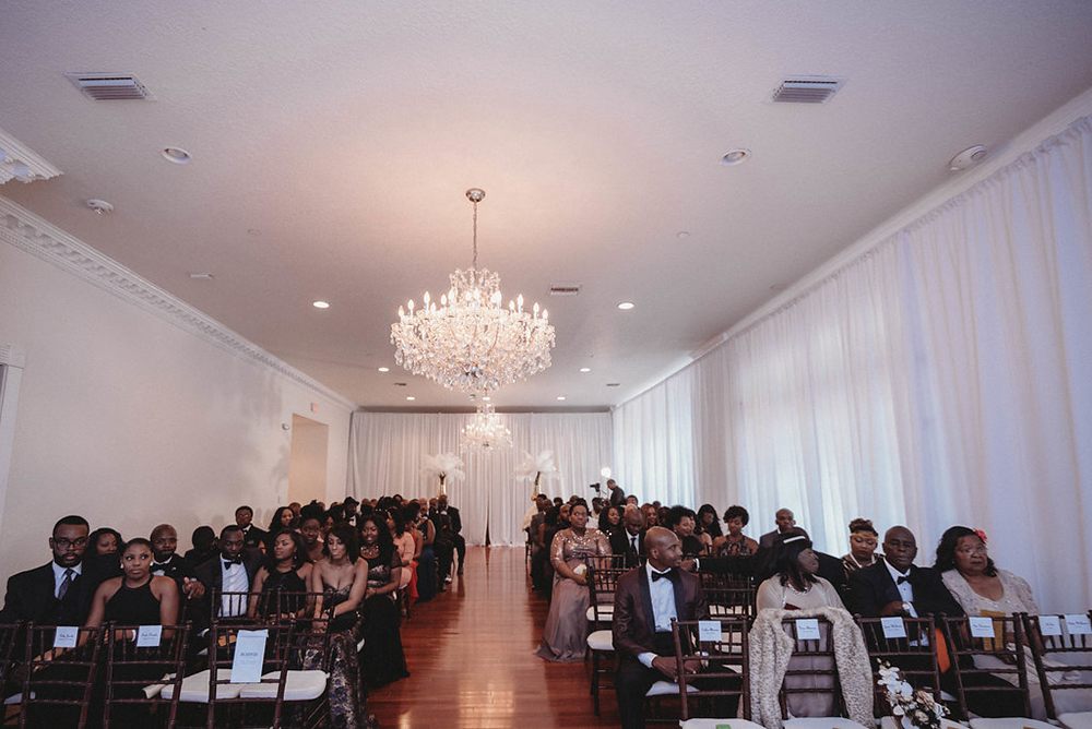 Ballroom wedding, indoor wedding venue, ceremony draping, luxury wedding venue, ballroom ceremony, all white wedding, white draping, floor to ceiling draping, chandeliers, feather centerpieces, mahogany chiavari chairs, central florida wedding venue
