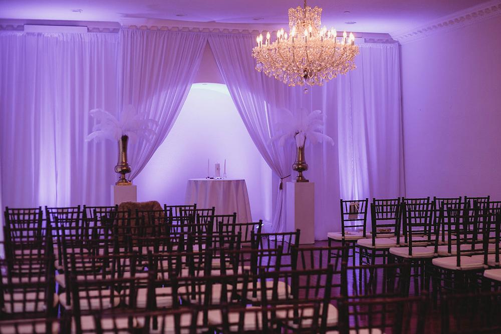 ballroom wedding, ceremony draping, indoor ceremony, Florida luxury weddings, feather centerpiece, central florida wedding venues, purple uplighting, luxury wedding