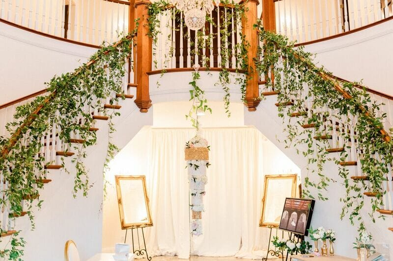 Elborate hanging white and gold wedding cake. Flanked by grand staircase featuring lush greenery.