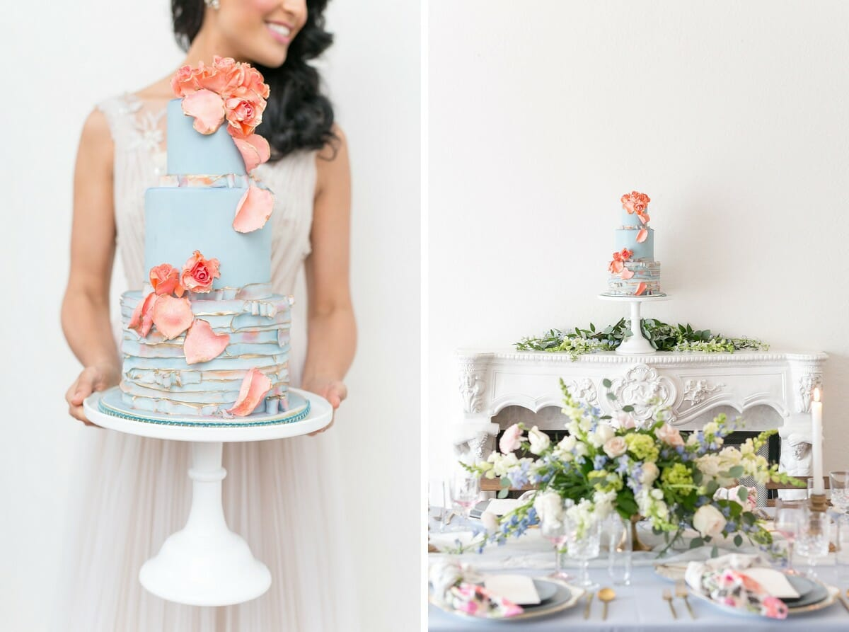 Blue three tiered wedding cake with coral pink flowers and petals, detailed with gold flecks.