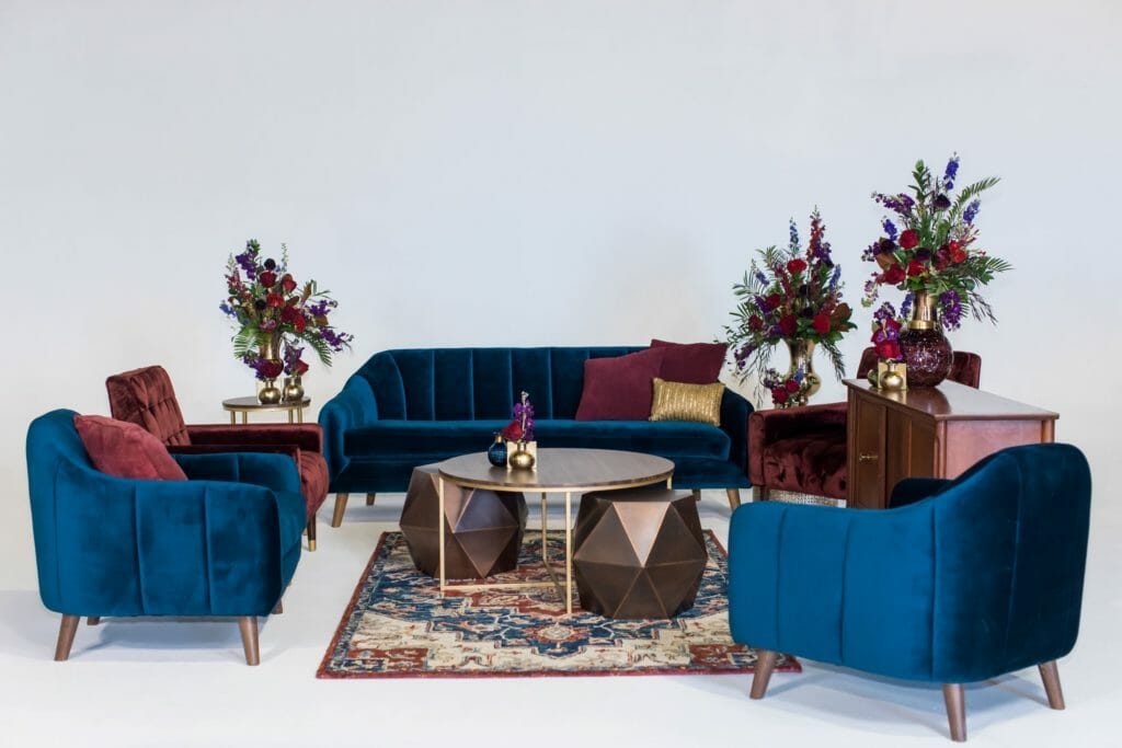 orlando lounge rental jewel tone bohemian inspired lounge with blue sofa and merlot chairs and a mid-century modern buffet