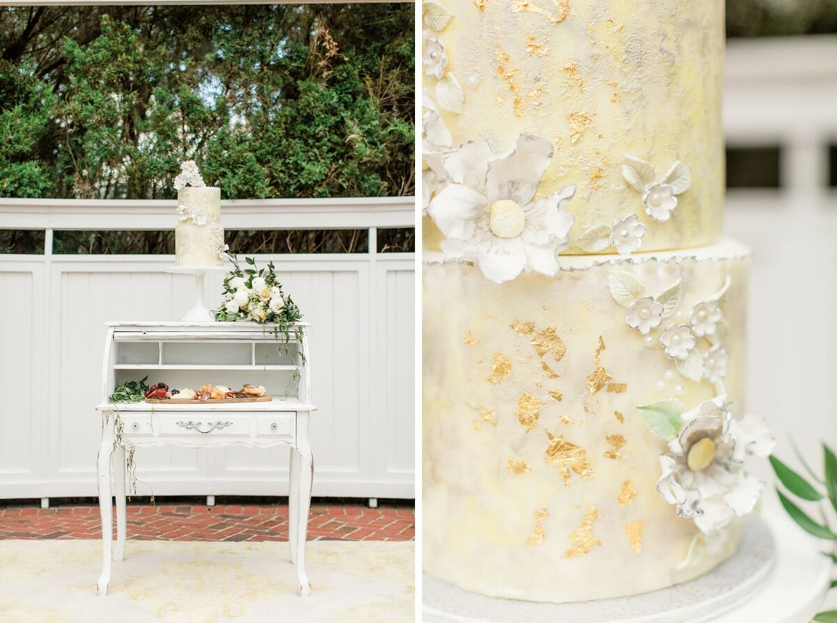 Creamy yellow marbled wedding cake with white and silver flecked sugar flowers. Atop a vintage white, roll-top desk.