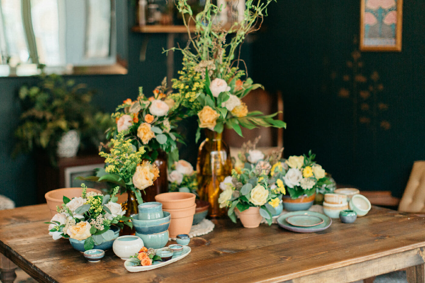 Eclectic decor including handmade pottery, amber vases, and pastel floral.