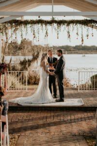 The couple saying their vows under the ceremony gazebo at Cypress Grove Estate. The gazebo is draped in floral garland and is set against a sunset on the lake.