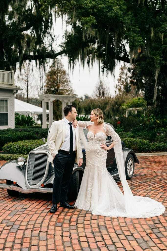 The bride and groom posing for a photo in front of a vintage car.