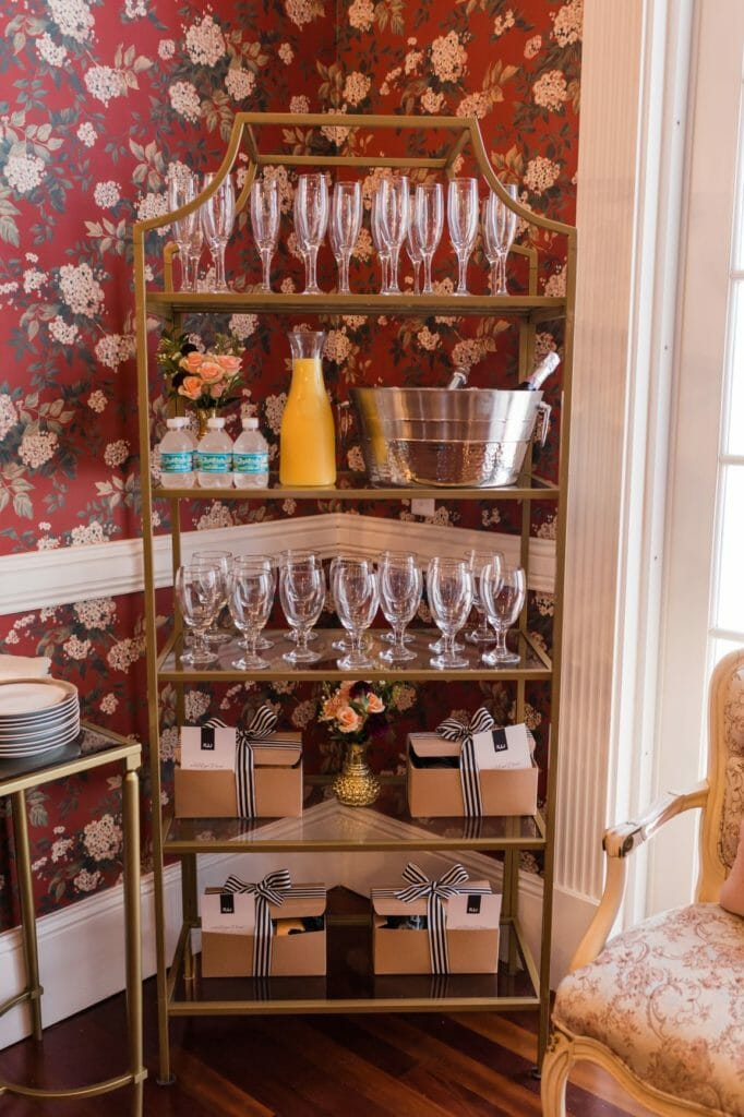 "Our Gwen bookshelf, featuring champagne flutes and water goblets, assorted beverages, and ""thank you"" gifts for our new vendor pals."
