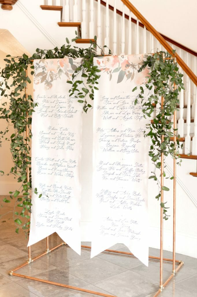 Seating Charts | Custom Fabric Hanging Seating Chart with calligraphy and garland.